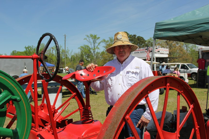 A member of the Wiggins family with a machine made from a hit and miss engine on an old tractor frame.